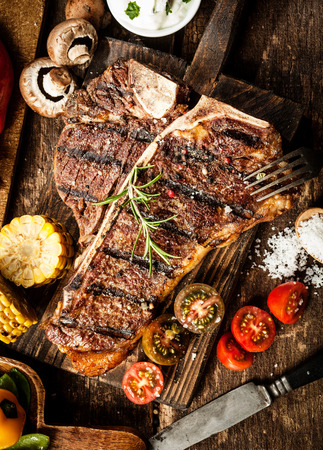 Grilled t-bone or porterhouse steak seasoned with rosemary in a rustic kitchen on a wooden board with tomatoes, corn, mushrooms and salt, overhead view