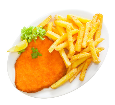 Golden crumbed veal schnitzel served with crisp potato chips or batons garnished with fresh frilly lettuce and lemon on a white platter, isolated on white