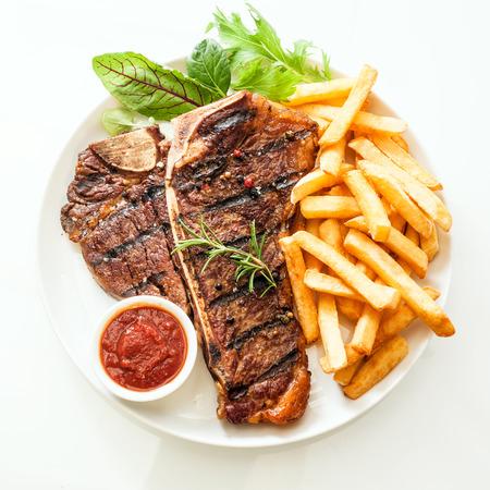Gegrilde T-bone of entrecôte gekruid met rozemarijn en geserveerd met gouden friet, verse groene kruiden salade en een tomaat dip, hoge hoek bekijken op wit Stockfoto