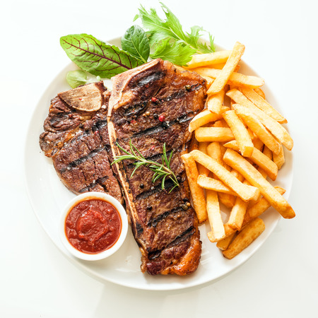 high angle view: Grilled t-bone or porterhouse steak seasoned with rosemary and served with golden French fries, fresh leafy herb salad and a tomato dip, high angle view on white