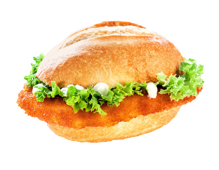 Tasty golden fried crumbed veal schnitzel or escalope bun topped with fresh green frilly lettuce and mayonnaise on white with clipping path