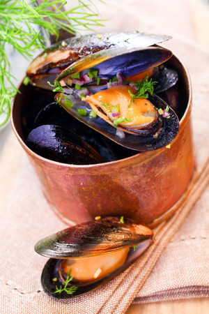high calorie foods: Delicious freshly boiled marine mussels in a copper saucepan with their shells open garnished with dill for a gourmet seafood starter, high angle closeup view