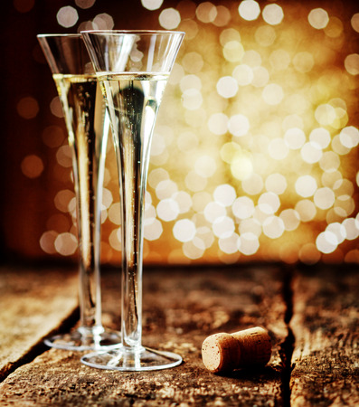 skoal: Two tall elegant flutes of romantic champagne on an old rustic wooden counter top against a sparkling bokeh of party lights celebrating a special occasion