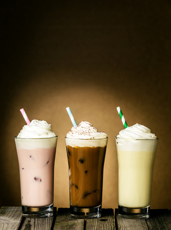 Three refreshing creamy milkshakes in berry, chocolate and lemon flavors topped with a twirl of ice cream or frozen yoghurt on a wooden table against a brown background with copyspace