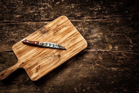 Empty chopping board with a sharp paring knife on a distressed grunge wooden table in a rustic kitchen, overhead view with a vignette and copyspace Stok Fotoğraf