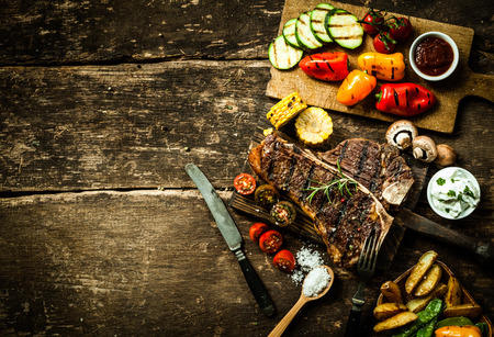 steaks: Overhead view of colorful roast vegetables, savory sauces and salt served with grilled t-bone steak on a rustic wooden counter in a country steakhouse Stock Photo