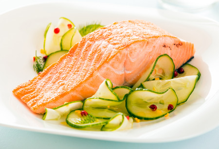 ovenbaked: Gourmet oven-baked pink salmon steak served with thinly sliced cucumber as a delicious seafood starter to a dinner