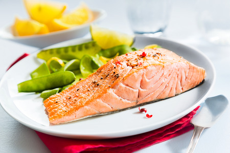 pink salmon: Gourmet seafood meal of grilled salmon steak served with fresh green mangetout peas and lemon wedges for flavoring Stock Photo