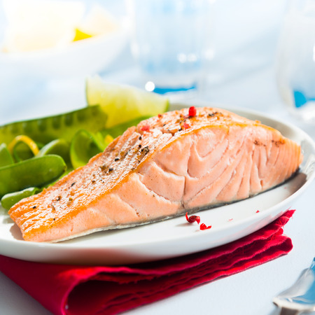 Healthy gourmet pink salmon steak rich in omega-3 served with fresh green mangetout peas and lemon, close up showing the texture of the fish photo