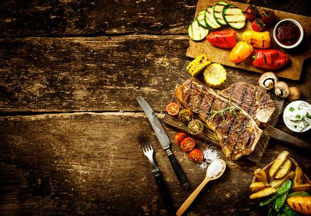 bistecche: Preparazione t-bone steak e verdure arrosto in una cucina rustica con peperoni, funghi, pomodori, patate, piselli mangiatutto, e mais su un tavolo di legno rustico con copyspace