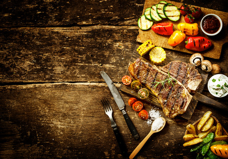 Preparing t-bone steak and roast vegetables in a country kitchen with bell peppers, mushrooms, tomato, potato, mangetout peas, and corn on a rustic wooden table with copyspace photo