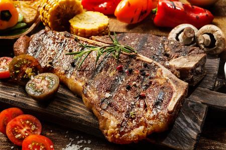 닫기 신선한 절반 토마토, 버섯, 옥수수 속대와 벨 고추 나무 보드에 후추와 로즈마리 양념 즙 부드러운 구운 비프 스테이크의 최대 스톡 콘텐츠