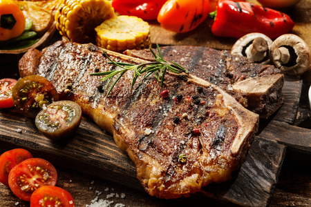 steaks: Close up of a succulent tender grilled porterhouse steak seasoned with pepper and rosemary on a wooden board with fresh halved tomatoes, mushrooms, corncobs and bell peppers
