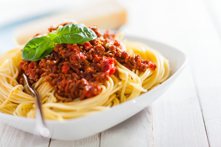 bolognaise: Dish of Italian spaghetti with rich tomato based Bolognaise sauce garnished with fresh basil leaves for a healthy Mediterranean diet