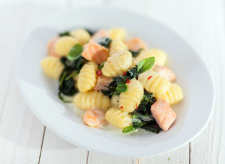 semolina pasta: Italian gnocchi pasta, or dumplings, sauteed and served with diced salmon and basil Stock Photo