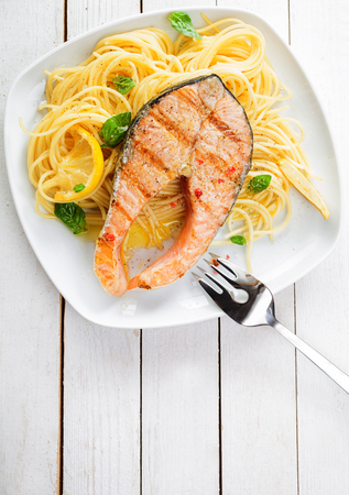 Gourmet seafood cuisine with grilled salmon cutlet steak served on a bed of Italian linguine pasta garnished with lemon and fresh basil, overhead view on a white wooden table with copyspace photo