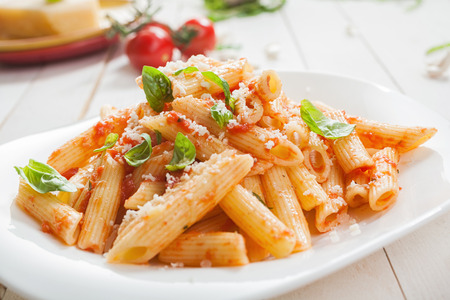 topped: Serving of spicy savory italian penne pasta garnished with fresh basil and topped with grated Parmigiano-Reggiano, or parmesan, cheese