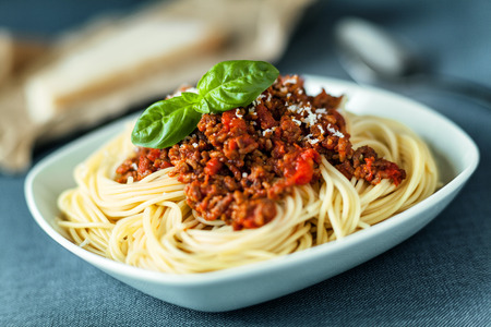Traditional Italian spahgetti Bolognaise or Bolognese with cooked pasta noodles topped with a spicy tomato based meat sauce garnished with fresh basil Stock Photo