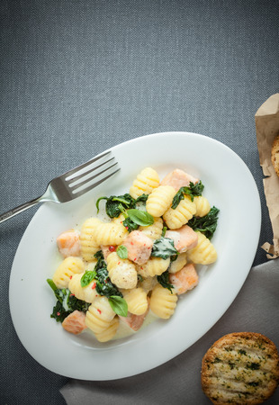 Traditional Italian cuisine with a plate of gnocchi pasta, or dumplings, made with semolina and served with basil and grilled salmon cubes, view from above on grey with copyspace photo