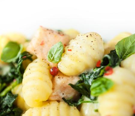 semolina paste: Pasta italiana gnocchi, o gnocchi a base di semola, con basilico e salmone, vista closeup condito con spezie