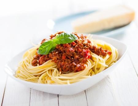 イタリアのスパゲッティのおいしいトマトと地面の牛のミートソースと素朴な白い木製のテーブルに新鮮なバジルをトッピングの健康板