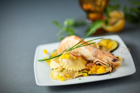 Ravioli and shrimp starter with stuffed round Italian girasole ravioli pasta, roasted aubergine and pink prawn or shrimp photo