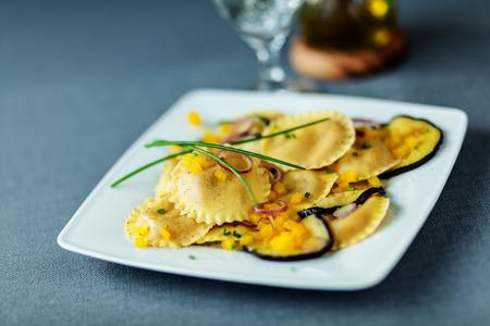 Vegetarische Italiaanse ravioli pasta met gegrilde of geroosterde plakjes aubergine of aubergine geserveerd op een moderne vierkante plaat gegarneerd met verse bieslook Stockfoto