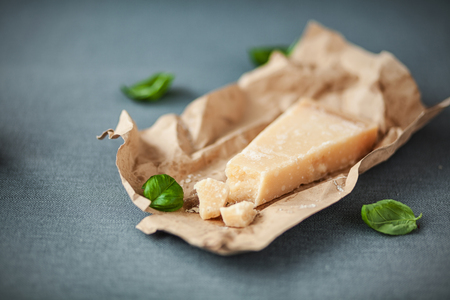 matured: Portion of mature Italian Parmesan cheese with a traditional hard granular texture with scattered fresh basil on crinmpled brown paper, on a grey cloth with copyspace Stock Photo