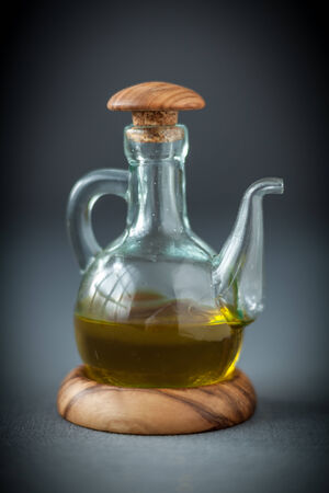 Transparent glass decanter with a wooden stopper half filled with healthy olive oil to use as a dressing for salads or cooking ingredient, on grey photo