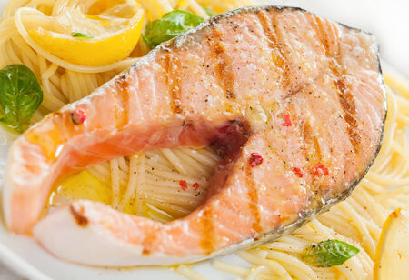 cooked fish: Grilled salmon cutlet with linguine pasta, basil and lemon for a gourmet Italian seafood dinner, close up view and texture Stock Photo
