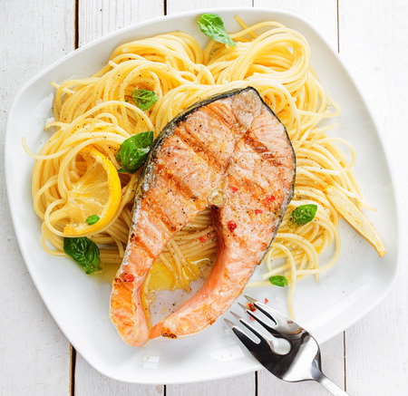 linguine pasta: Healthy grilled salmon steak rich in omega-3 fatty acids served on linguine pasta topped with fresh basil , overhead view