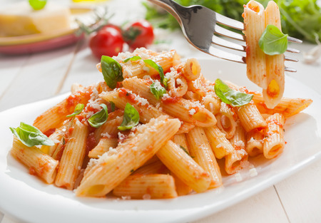 pasta salad: Delicious savory Italian penne rigate pasta with fresh basil and grated parmesan cheese served with a salad with a fork with two pasta tubes suspended above the plate