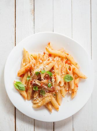 plate of food: Vista dall'alto di un sano piatto di pasta penne italiana con basilico, santoreggia salsa piccante e parmigiano grattugiato rustiche tavole di legno bianco con copyspace
