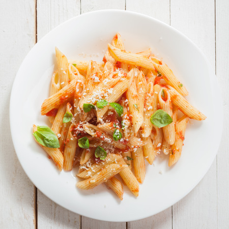 high angle view: Italian penne pasta or noodles with a savory tomato sauce, fresh basil and grated parmesan cheese viewed close up from above on a white plate in square format