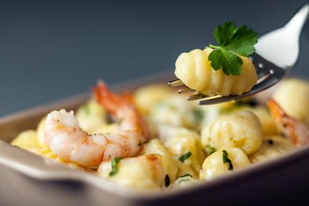semolina paste: Pasta gnocchi italiana, o gnocchi a base di semola, con gamberi o gamberetti per una deliziosa cucina di pesce con uno gnocco su una forcella con messa a fuoco selettiva Archivio Fotografico
