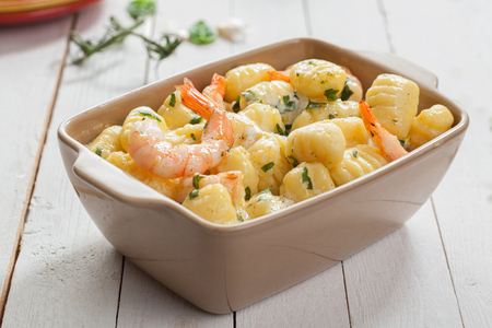 Tasty Italian seafood cuisine with grilled pink prawns in gnocchi pasta, or semolina dumplings, served in a casserole seasoned with fresh herbs Archivio Fotografico