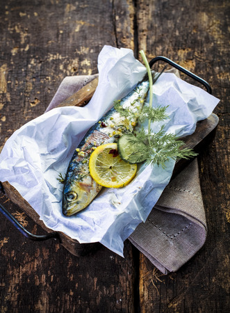 Delicious seafood dinner of whole baked fish with a seasoning of assorted fresh herbs, lemon and spices, view from above on a rustic wooden kitchen counter