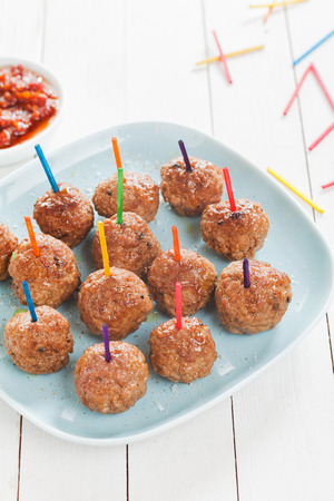 plateful: Preparing a tray of delicious spicy seasoned meatballs with colored toothpicks for snacks at a catered event , high angle view on a plate on rustic white boards