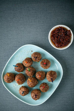 plateful: Overhead view of a plateful of seasoned meatballs and savory spicy tomato and chili pepper dip for appetizers, overhead view on a grey tablecloth with copyspace