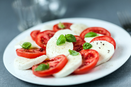 alternating: Healthy Italian Caprese salad served on a plate with alternating slices of white mozzarella cheese and ripe red tomato topped with fresh basil