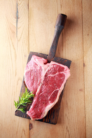 meat counter: Raw t-bone or porterhouse steak with a sprig of fresh rosemary on a vintage wooden board , overhead view on wood with copyspace