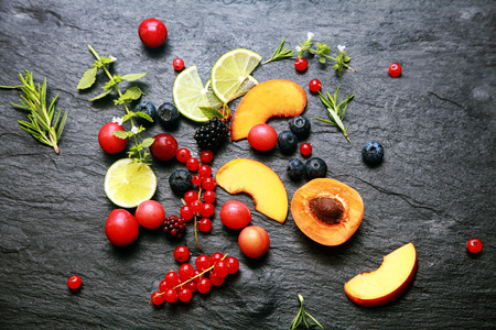 Scattered fresh fruit and berries with cranberries, blackberries, redcurrants, lemon, peach, blueberries, rosemary and herbs on a textured slate background