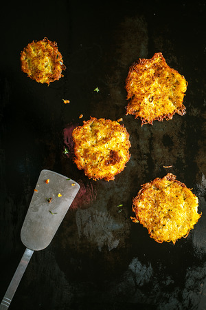 fritters: Delicious golden fried potato fritters made with grated potatoes frying on a hot griddle with a metal spatula to be served as an accompaniment to a meal Stock Photo