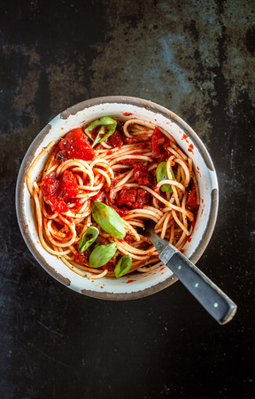 top down: Overhead view of a tasty serving of Italian spaghetti for a country lunch in an old metal bowl on a dark slate background with copyspace