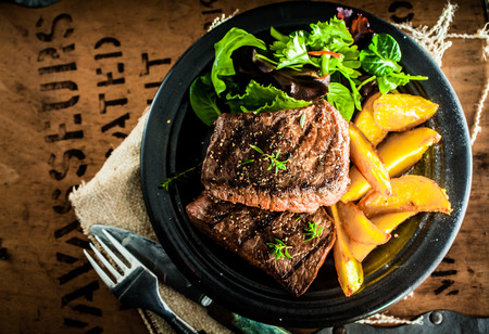 meal preparation: Overhead view of delicious,grilled beef steak with roasted pumpkin and fresh green herb salad on an old wooden packing case with printed text