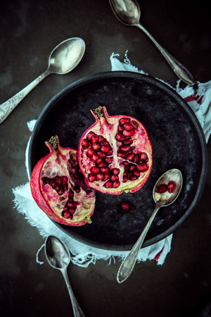 top down: View from above of a fresh halved pomegranate on a plate showing the juicy ripe red sweet seeds with spoons for eating on a dark background