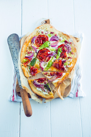 alsation: Savory Tarte Flambee a gastronomical delicacy from the Alsace region of France with a thin crispy pastry base topped with creme fraiche or cheese, lardons or bacon cubes, onions, herbs and tomato