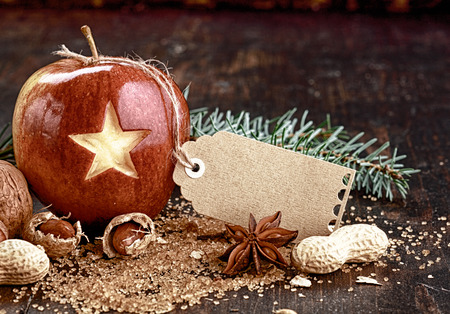 Blank Tag on Christmas Apple Ready for Greetings on Wooden Table photo