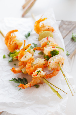 prawn skewers: Prawn or shrimp kebab appetizer with grilled pink prawn on skewers with lemon and fresh herbs for a delicious start to a meal