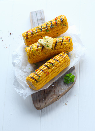 mealie: Grilled corn on the cob topped with a butter curl and served at a summer outdoor picnic on crumpled white paper on a wooden board